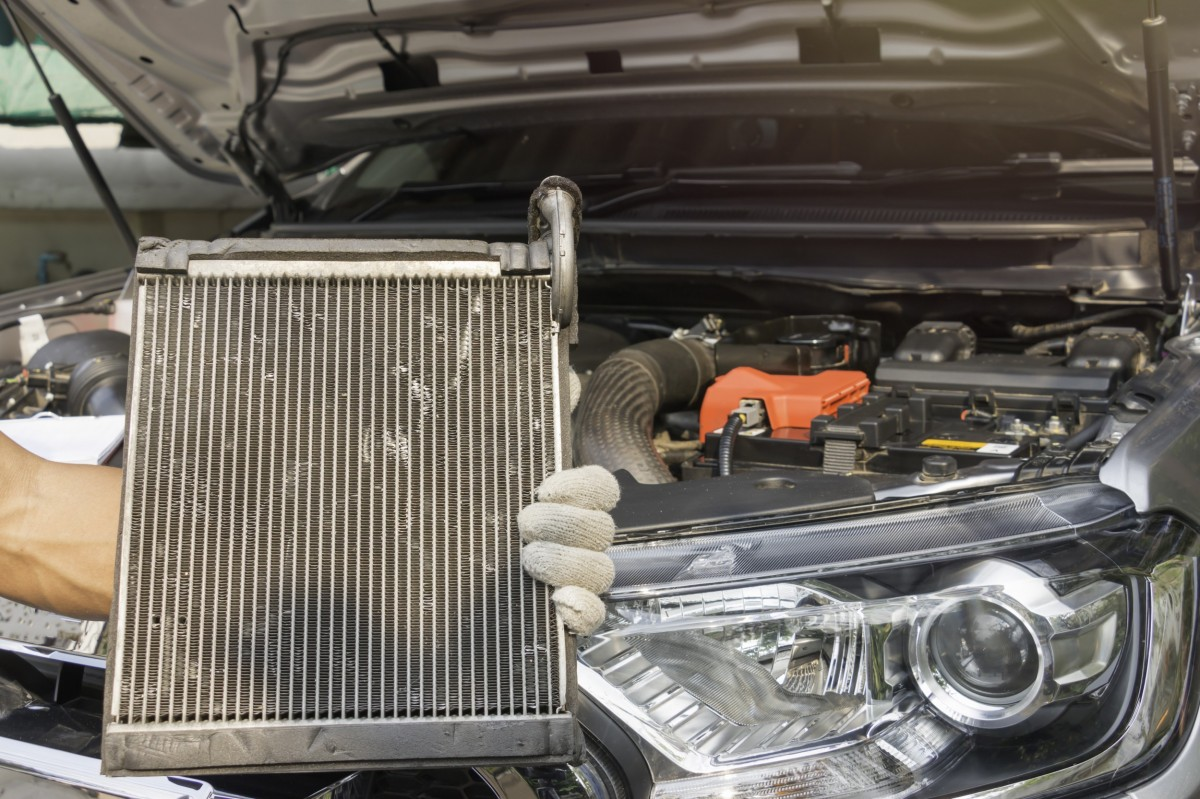 hand holding radiator in front of car with hood up